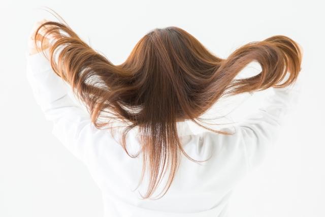 髪をかきあげる女性の画像