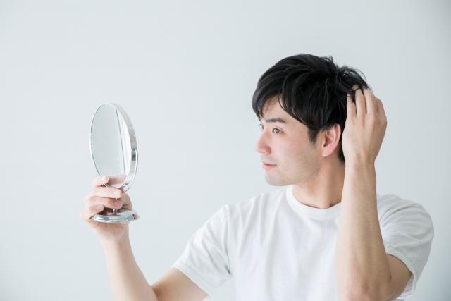 頭皮を気にする男性の画像